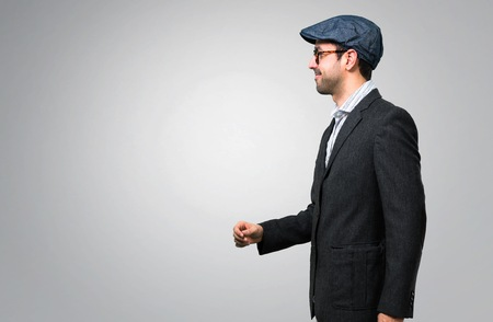 Handsome modern man with beret and glasses walking on grey background