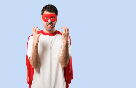 Superhero man with mask and red cape annoyed angry in furious gesture. Negative expression on isolated blue background