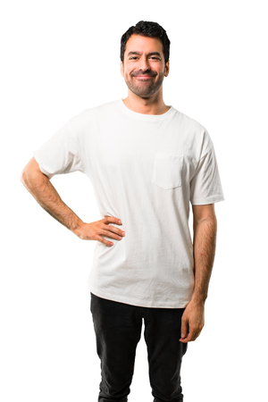 Young man with white shirt posing with arms at hip and smiling on isolated white background