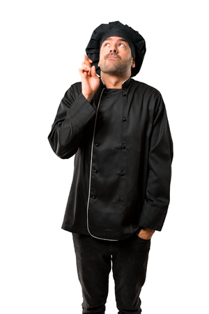 Chef man In black uniform with fingers crossing and wishing the best. Making a wish. on isolated white background Stock Photo