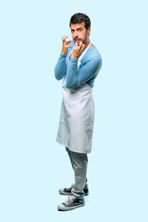 Full body of Man wearing an apron annoyed angry in furious gesture. Negative expression on blue background