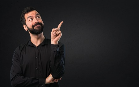 Handsome man with beard thinking on black background Stock Photo