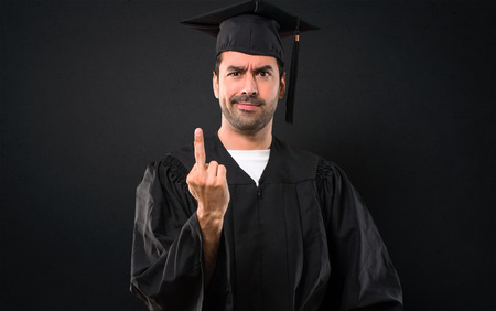 Man on his graduation day University making horn gesture. Negative expression on black background