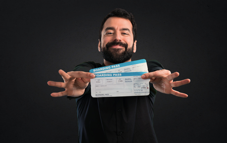 Handsome man with beard holding air tickets on black background