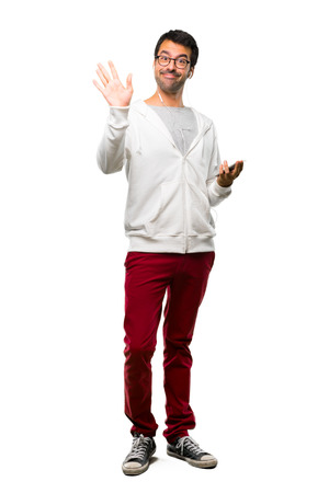 Full body of Man with glasses and listening music saluting with hand with happy expression on white background Stock Photo