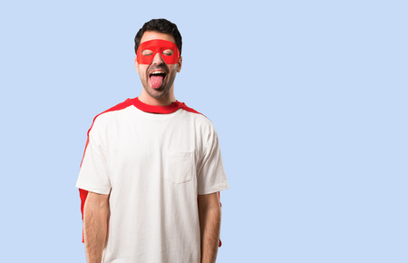 Superhero man with mask and red cape showing tongue at the camera having funny look on isolated blue background