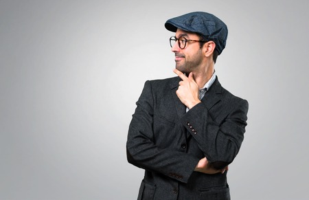 Handsome modern man with beret and glasses standing and looking to the side on grey background