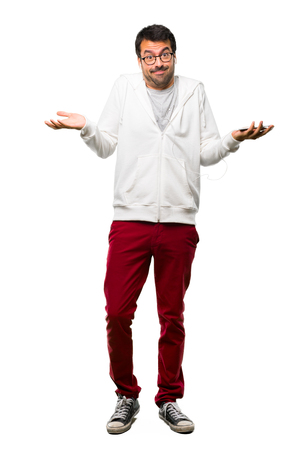 Full body of Man with glasses and listening music making unimportant and doubts gesture while lifting the shoulders and the palms of the hands on white background Stock Photo