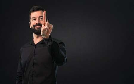 Handsome man with beard touching on transparent screen on black background