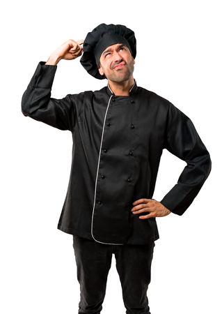 Chef man In black uniform having doubts and with confuse face expression while scratching head on isolated white background Stock Photo
