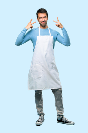 Full body of Man wearing an apron showing tongue at the camera having funny look on blue background Stock Photo