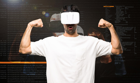 Man using VR glasses making strong gesture inside the virtual reality mode Stock Photo