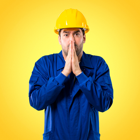 Young workman with helmet keeps palm together. Person asks for something on yellow background