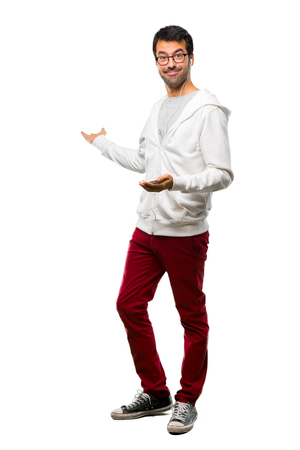 A full-length shot of a Man with glasses and listening music pointing back with the index finger presenting a product on white background