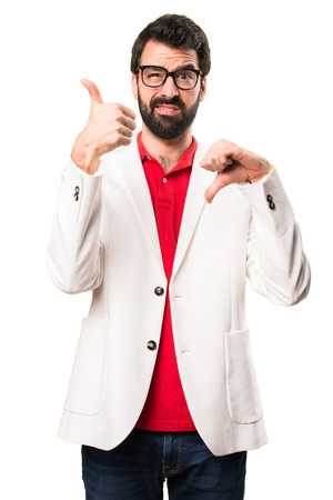Brunette man with glasses making good-bad sign on white background