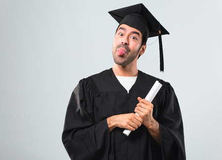 Man on his graduation day University makes funny and crazy face emotion on grey background