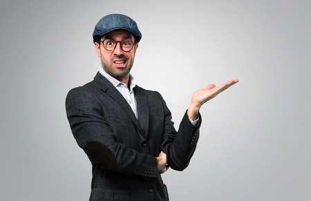 Handsome modern man with beret and glasses unhappy and frustrated with something. Negative facial expression on grey background