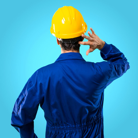 Young workman with helmet on back position looking back while scratching head on blue background Stock Photo