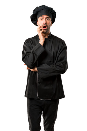 Chef man In black uniform surprised and shocked while looking right. Expressive facial emotion on isolated white background