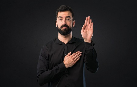 Handsome man with beard making an oath on black background