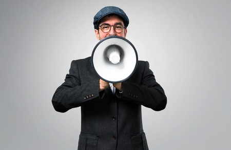 fac0ece00397c Handsome modern man with beret and glasses holding a megaphone on grey  background