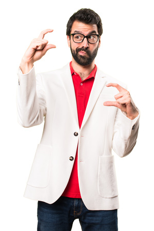 Brunette man with glasses making tiny sign on white background