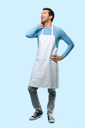 Full body of Man wearing an apron standing and thinking an idea while scratching head on blue background