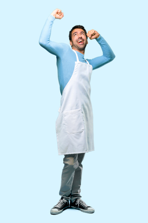 Full body of Man wearing an apron celebrating a victory and surprised to be successful on blue background