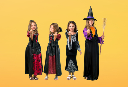 Set of Little girl dressed as a vampire for halloween holidays presenting and inviting to come on orange background