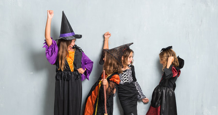 Group of friends with costumes of vampires and witches for halloween holidays making victory gesture Stok Fotoğraf