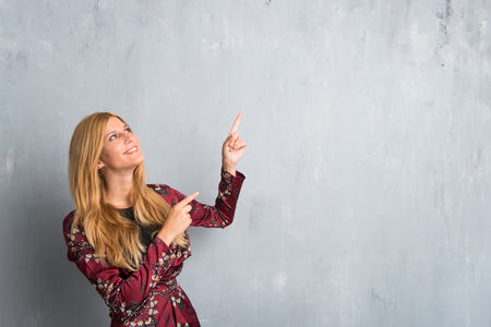 Blonde woman pointing with the index finger a great idea and looking up on textured wall background