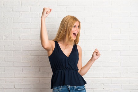 Blonde woman celebrating a victory and happy for having won a prize on white brick wall background