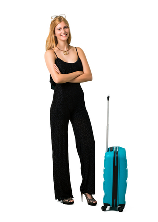 Blond girl traveling with her suitcase keeping the arms crossed in frontal position. Confident expression on isolated white background