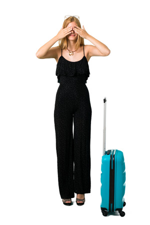 Blond girl traveling with her suitcase covering eyes by hands. Do not want to see something on isolated white background Imagens