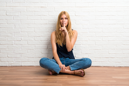 Blonde girl sitting on the floor showing a sign of closing mouth and silence gesture on white brick wall background