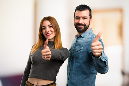 Man and woman with thumb up on unfocused background