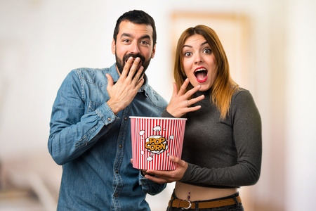 Man and woman eating popcorns on unfocused background Imagens