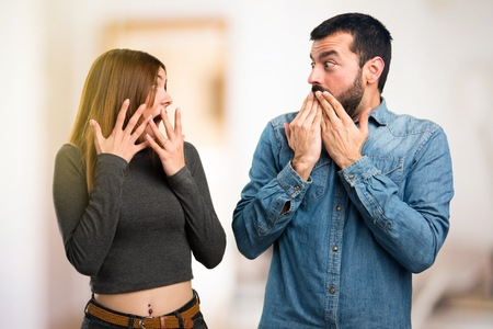 Man and woman making surprise gesture on unfocused background
