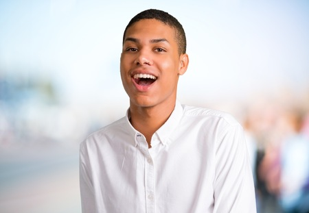 Young african american man with surprise and shocked facial expression. Gaping because have just surprised with a gift on unfocused outdoor background