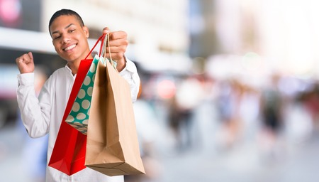 Young african american man with white shirt holding a lot of shopping bags in the middle of the city