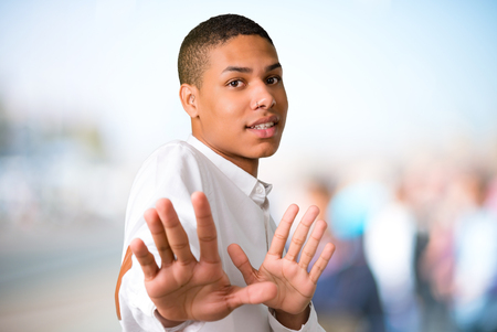 Young african american man is a little bit nervous and scared stretching hands to the front on unfocused outdoor background