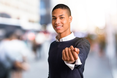Young african american man presenting and inviting to come in the middle of the city