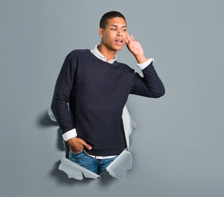 Young african american man listening something through a paper hole Imagens