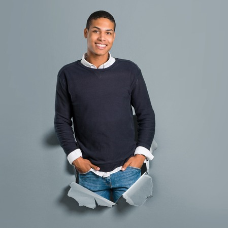 Young african american man laughing through a paper hole