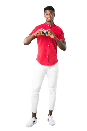 Full body of Young african american man holding a camera on white background Foto de archivo