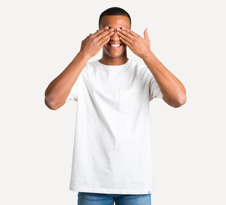 Young african american man covering eyes by hands. Surprised to see what is ahead on isolated background