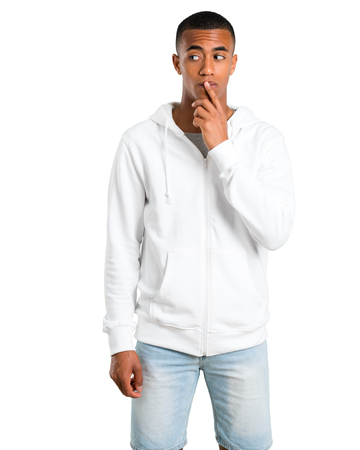 Dark-skinned young man with white sweatshirt having doubts and with confuse face expression while looking up. Questioning an idea on isolated white background