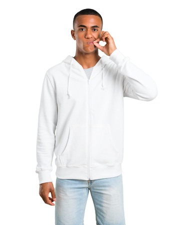 Dark-skinned young man with white sweatshirt showing a sign of closing mouth and silence gesture doing like closing his mouth with a zipper on isolated white background Banque d'images