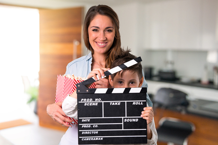 Mother and daughter holding a clapperboard inside house Stockfoto