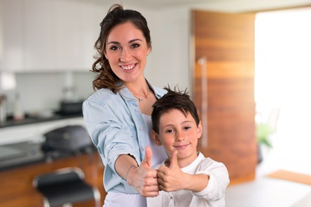 Mother and daughter giving a thumbs up gesture and smiling inside house Banco de Imagens